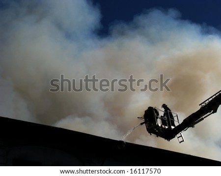 Two firemen standing on a snorkel spraying water onto the fire - stock photo