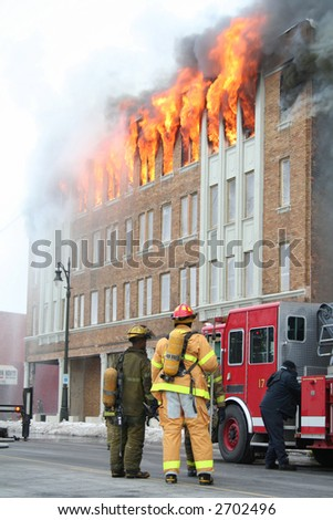 Two Firemen watching an apartment on fire - stock photo