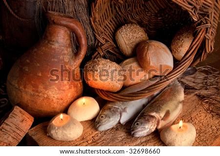 Two fish and five loaves of bread with candle-light and an antique wine jar - stock photo