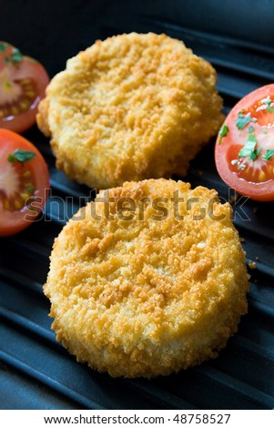 Two fish cakes on metal hot grill with tomatoes - stock photo