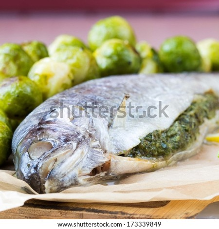 Two fish, rainbow trout stuffed with green herb sauce, Brussels sprouts garnish, delicious dinner - stock photo