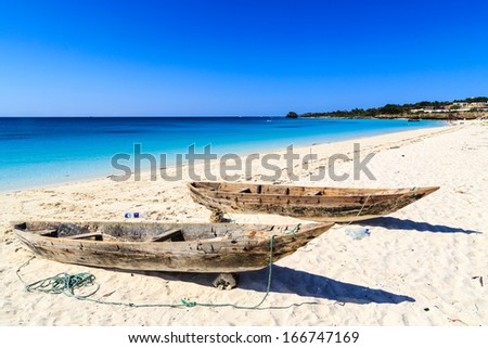 Two fisherman boats on the beach with blue sky - stock photo