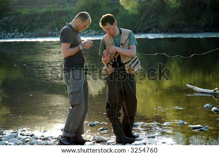 Two fisherman make ready angling on the river - stock photo