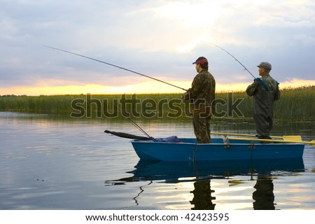 two fisherman on boat. catching pike - stock photo