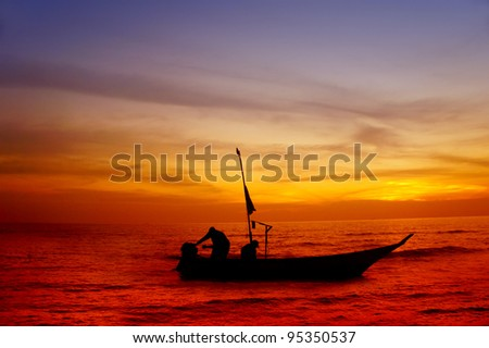two fisherman silhouette in the boat - stock photo