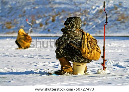 Two Fishermen Fish in the Winter - stock photo