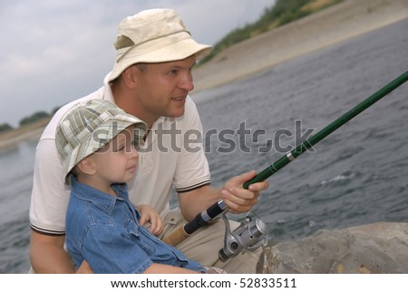 Two fishermen from a fishing rod - stock photo