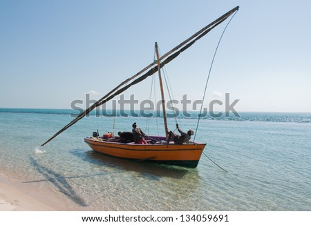 Two fishermen hoist the sail high up in the mast of a traditional dhow which floats in the lagoons of the Bazaruto Archipelago in Mozambique. - stock photo