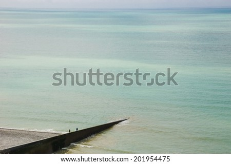 Two fishermen on old concrete pier. Mers-les-Bains (Picardy, France) - stock photo