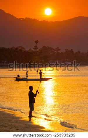 Two fishermen, one in the boat, the other standing on the beach go fishing at sunset