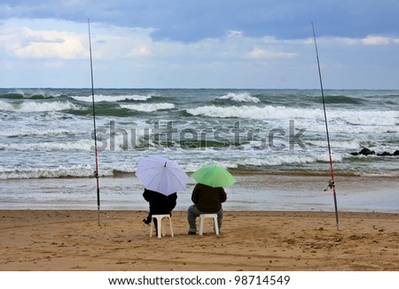 Two fishermen with umbrellas in storm - stock photo