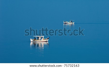 Two fishing boats traveling in opposite directions on calm Greek waters during a peaceful morning - stock photo