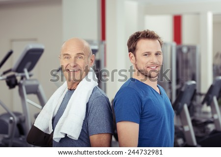 Two fit healthy men posing back to back at the gym, one senior and one young, looking at the camera with smiles full of vitality in a health and fitness concept - stock photo