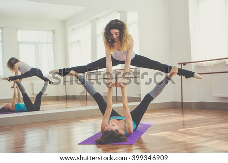 Two fit women are doing balance exercise - stock photo