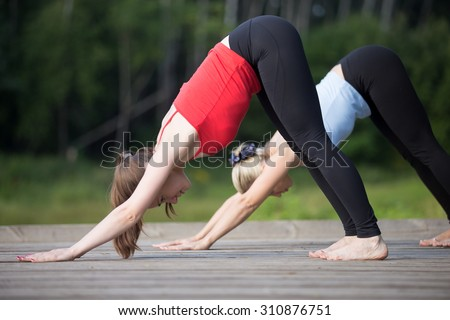 Two fit young beautiful women working out outdoors in park on summer day, wearing sportswear red and blue tank tops, doing downward facing dog posture, surya namaskar complex - stock photo