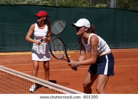 Two fit, young, tanned and healthy women playing doubles at tennis in the sun on a red asphalt court on vacation - stock photo
