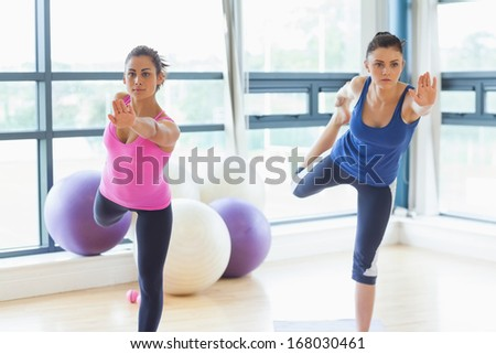 Two fit young women doing the balancing yoga pose in a bright fitness studio