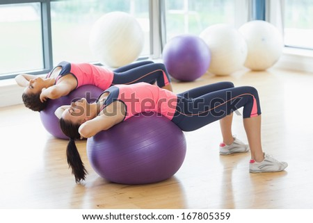 Two fit young women stretching on fitness balls in the bright gym
