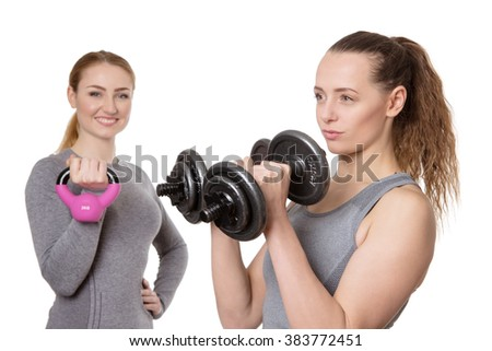 two fitness woman working out one using dumbbells the other a kettebell