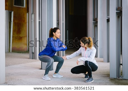 Two fitness women doing squat exercise workout outdoor. Female coach correcting knee position for legs exercising. - stock photo