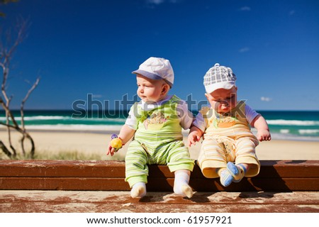 Two five months old brother twins sitting on a beach jetty - stock photo