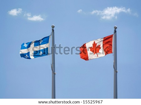Two flags floating in the sky : Quebec and Canada - stock photo