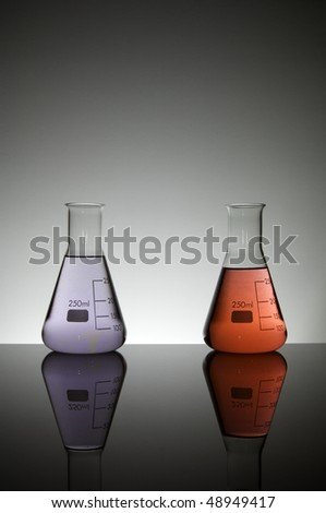 two flasks containing liquid purple and red on a white background