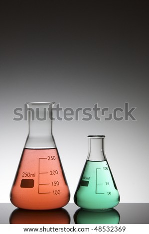 two flasks with liquid red and green on a white background