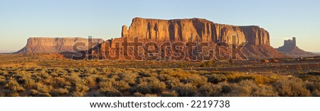 Two flat mesas and a vertical one are sailing through the Monument Valley at cold November dawn, showing off the sediment layers from millions of years ago (Navajo Nation, Utah). - stock photo