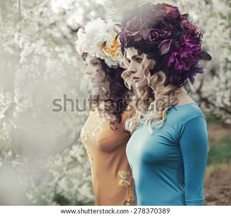 Two flower nymphs in a spring orchard - stock photo
