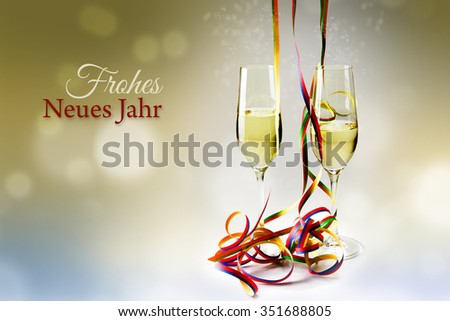Two flutes champagne glasses and colorful streamers decoration against a bokeh background, german text Frohes Neues Jahr, that means happy new year - stock photo