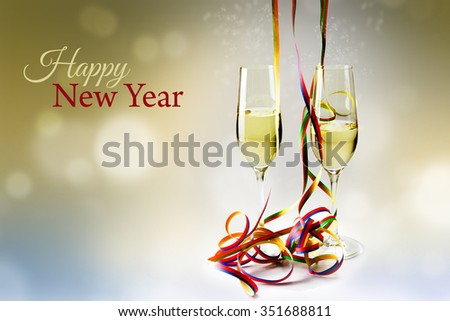 Two flutes champagne glasses and colorful streamers decoration against a bokeh background, text happy new year - stock photo