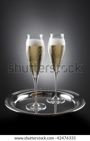 Two flutes of champagne filled and shot on silver serving tray - stock photo