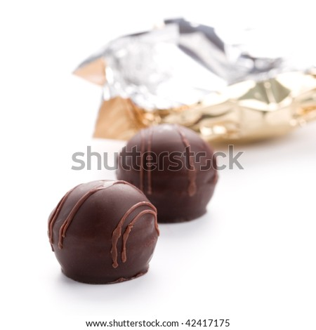 two foil opened sweets on white background - stock photo