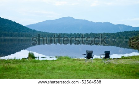 Two foldable camping chair on a mountain lake shoreline in the evening - stock photo
