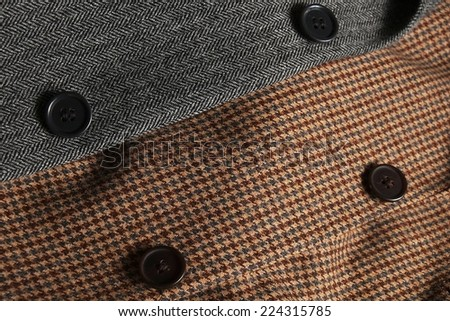 Two folded gray and brown woolen tweed coats overlapping diagonally - stock photo