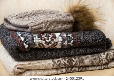 Two folded winter sweaters and woolen hat with bubo neatly arranged on each other - stock photo