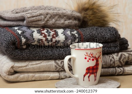 Two folded winter sweaters, woolen hat with bubo and a cap with ornament - stock photo