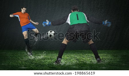 Two football players in action under rain in stadium