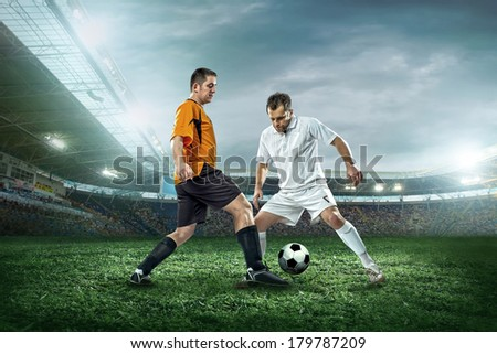 Two football players with ball in action outdoors. - stock photo