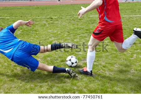 Two footballers chasing ball on grass-field during game - stock photo