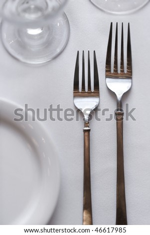 Two forks sitting on a dining table with a white tablecloth. Vertical shot.