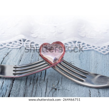 two forks with little heart, concept of love - stock photo