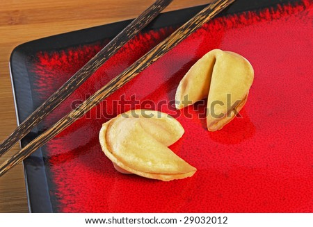 Two fortune cookies on a red plate with chop sticks - stock photo