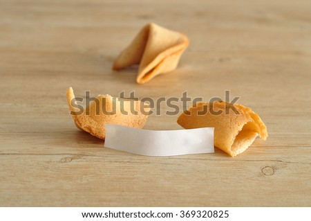 Two fortune cookies  - one broken open with a white piece of paper for your fortune - displayed on a wooden background