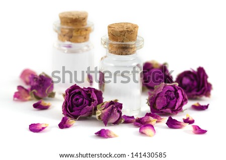 Two fragrance bottles filled with rose aroma oil with purple dried rose buds and petals isolated on white background. - stock photo