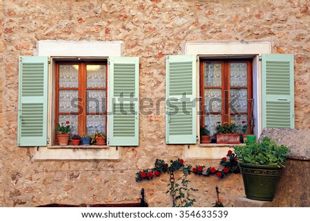 Two french rustic windows with old green shutters and flower pots in stone rural house, Provence, France. - stock photo