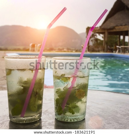 Two fresh and tasty mojito with swimming pool background in tropical hotel - stock photo