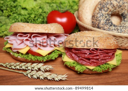 Two fresh bagels with salami and ham as well as cheese, tomatoes and lettuce - stock photo