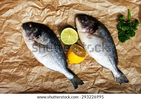 Two fresh chef Dora is going to marinate with lemon, salt and a large bunch of parsley - stock photo